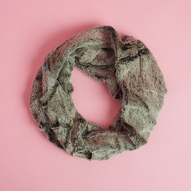 brownish furry circle scarf laying on pink table