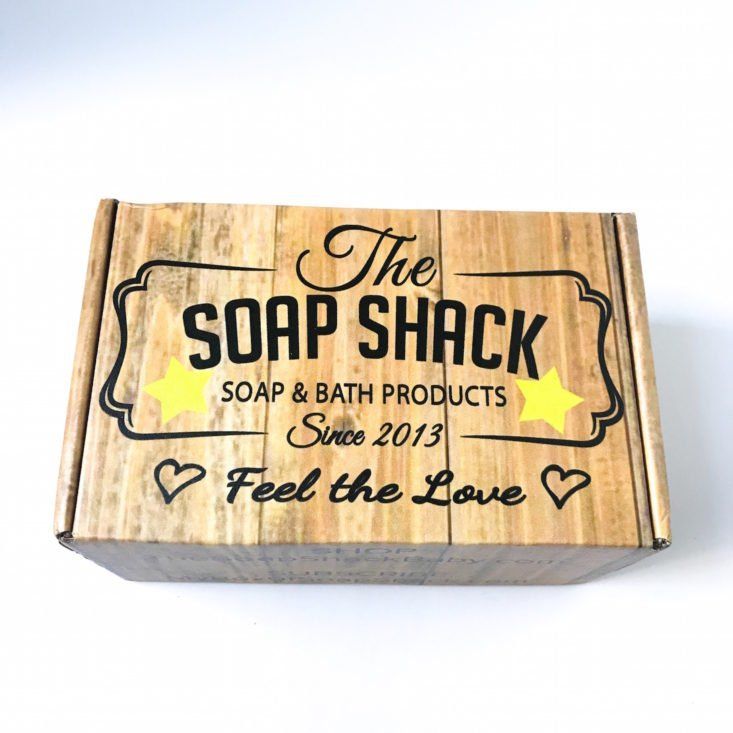 closed shipping box with the words The Soap Shack Soap & Bath Products Since 2013, Feel the Love printed in black
